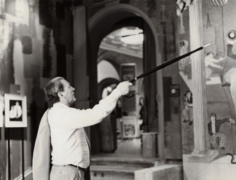 Richard Buckle during the installation of 'Happy and Glorious: 130 Years of Royal Photographs', by Ernestine ('Nesta') MacDonald (née Rosse), 1977 - NPG x134697 - © reserved; collection National Portrait Gallery, London