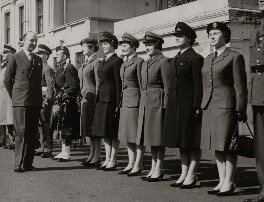 John Profumo inspecting some of the uniforms worn by members of the Women's Services, by Unknown photographer - NPG x196132