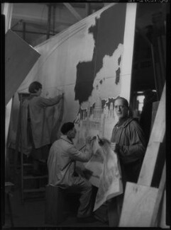 Macdonald Gill with two assistants working on 'Decorative Map of the Atlantic' for RMS Queen Mary, by Howard Coster - NPG x14552