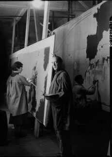 Macdonald Gill with two assistants working on 'Decorative Map of the Atlantic' for RMS Queen Mary, by Howard Coster - NPG x14553