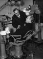 Sir (Howard) Kingsley Wood trying out a dentist's chair at a public health exhibition., by Harold Tomlin, for  Daily Herald - NPG x88277
